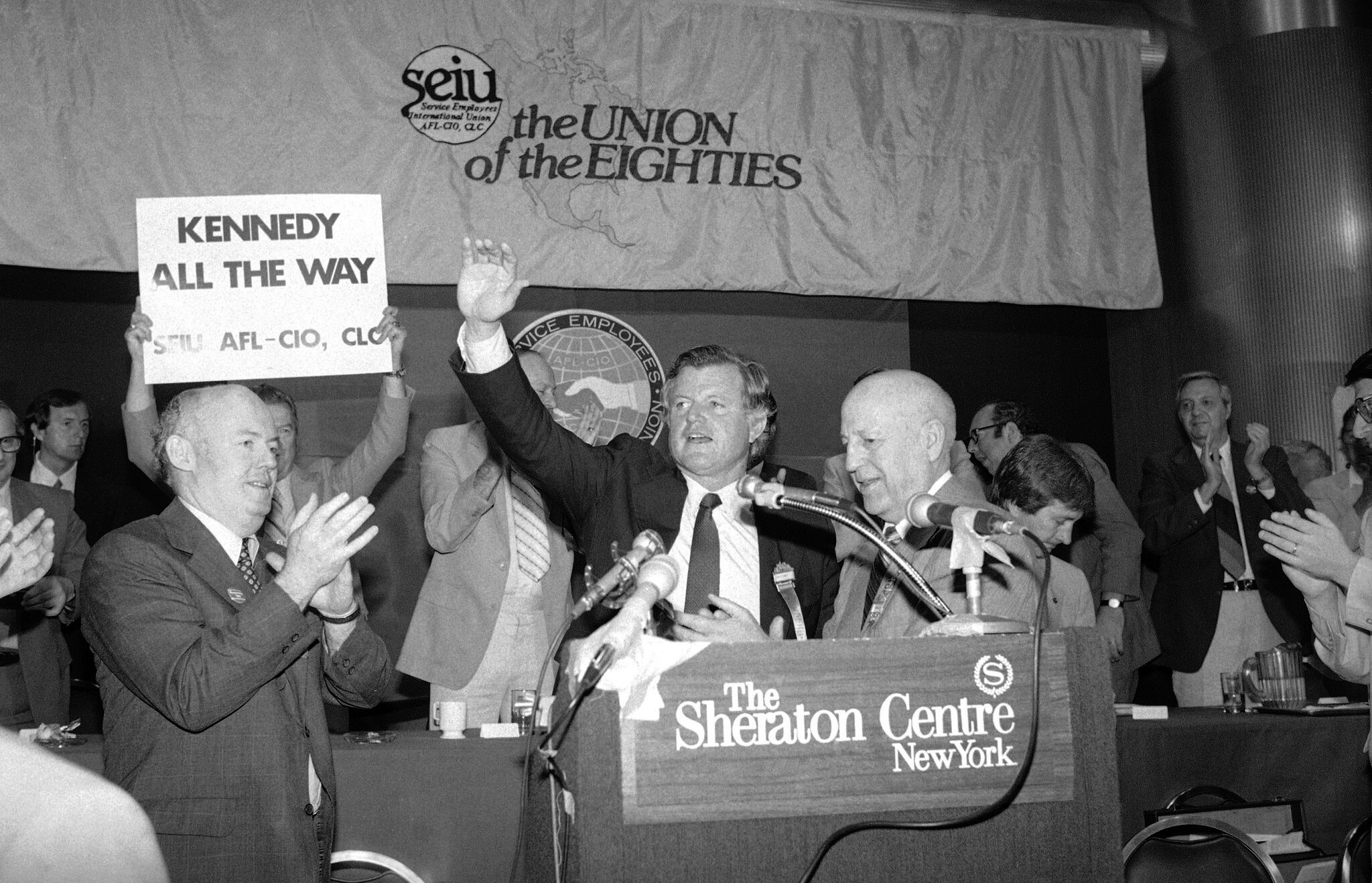 John Sweeney, left, was the incoming president of the Service Employees International Union in June 1980 when Senator Edward M. Kennedy (waving) spoke to its convention in New York. Mr. Kennedy was seeking the Democratic presidential nomination. At right in the foreground was the outgoing union president, George Hardy. Credit: Associated Press
